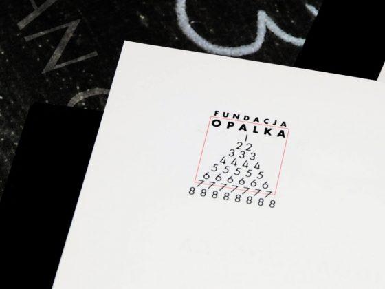 Logo Fundacji Opałka (lata 90-te). Projekt zrealizowany przez wydawcę O.pl, wydawnictwo MODULUS w ścisłej współpracy z Romanem Opałką, podkreśla ważność siedmiu siódemek w kontekście twórczości artysty