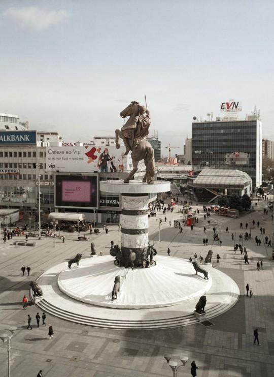 Najważniejszy nowy pomnik miasta Skopje – a także nieoficjalny symbol poszukiwania przez kraj nowej tożsamości – to niesławny Wojownik na Koniu. Odsłonięcie tego 24-metrowego monumentu odbyło się w 2012 roku z okazji 20. rocznicy uzyskania przez Macedonię niepodległości. Symboliczny gest na nowo rozpalił trwający od dawna konflikt z Grecją dotyczący zadziwiającego podobieństwa statuy do znanego powszechnie wizerunku Aleksandra Wielkiego. Grecki rząd konsekwentnie sprzeciwia się roszczeniom innych państw do tej historycznej postaci, uważając starożytnego władcę za część wyłącznie greckiego dziedzictwa. Spór o tożsamość kulturową, a także nierozstrzygnięte dyskusje dotyczące nazwy Macedonii zaowocowały działaniami ze strony Grecji, które zablokowały przystąpienie Macedonii do NATO i UE, a także skazały ją na długotrwałą izolację polityczną. Skopje, 2013 (źródło: dzięki uprzejmości artysty)