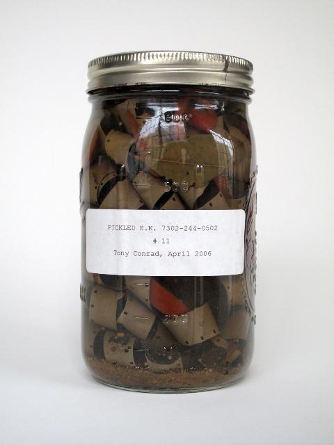Tony Conrad, Pickled E.K. 7302-244-0502/Zamarynowany E.K. 7302-244-0502, Film 16 mm zamarynowany w słoiku z octem, warzywami i przyprawami, 2006, 17.1x10.2x10.2 cm, dzięki uprzejmości artysty i galerii Greene Naftali, Nowy Jork