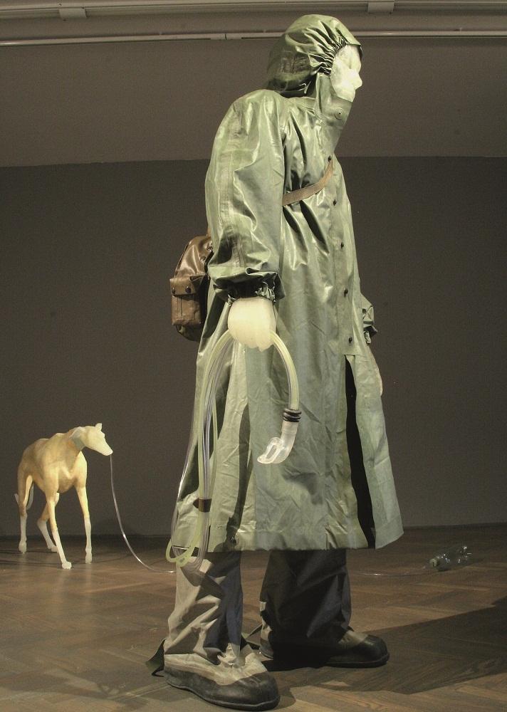 """Kuba Bąkowski, """"Chłopiec i jego pies"""", żywica epoksydowa, styropian, wojskowe gumowe ubrania ochronne, plastik, 2006 (źródło: materiały prasowe organizatora)"""