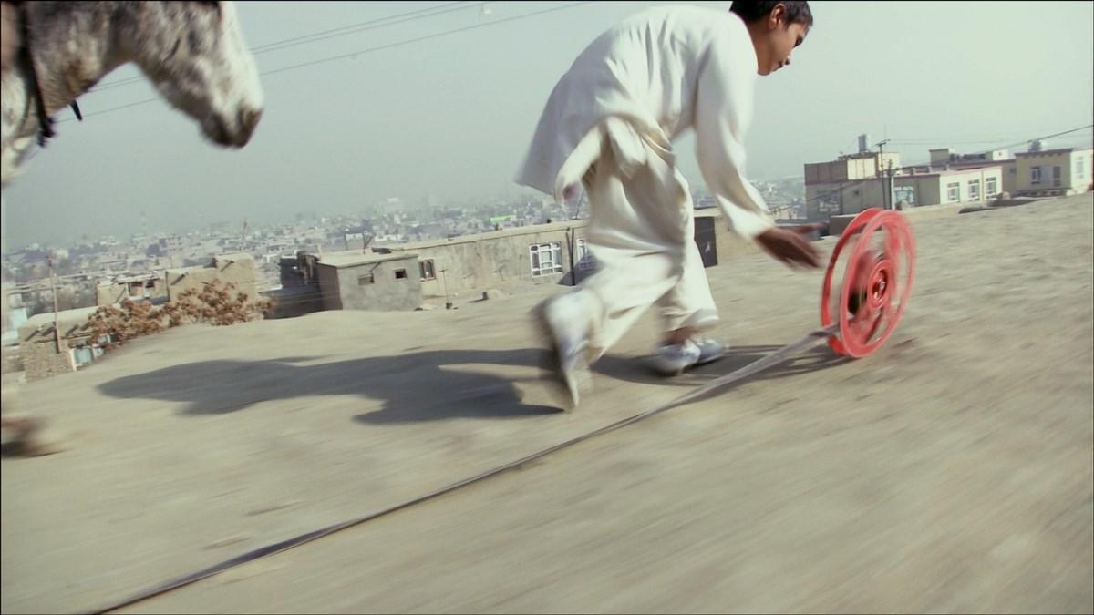 """Francis Alÿs, """"Reel-Unreel"""", dokumentacja wideo akcji, kadr z filmu, 2011. We współpracy z Julienem Devaux i Ajmalem Maiwandim (źródło: materiały prasowe organizatora)"""