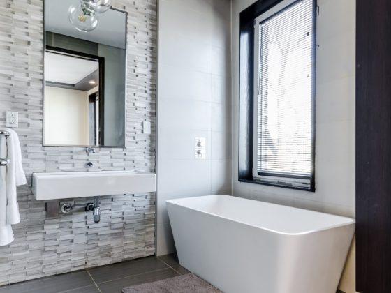 Biała prostokątna wanna w rogu minimalistycznej łazienki