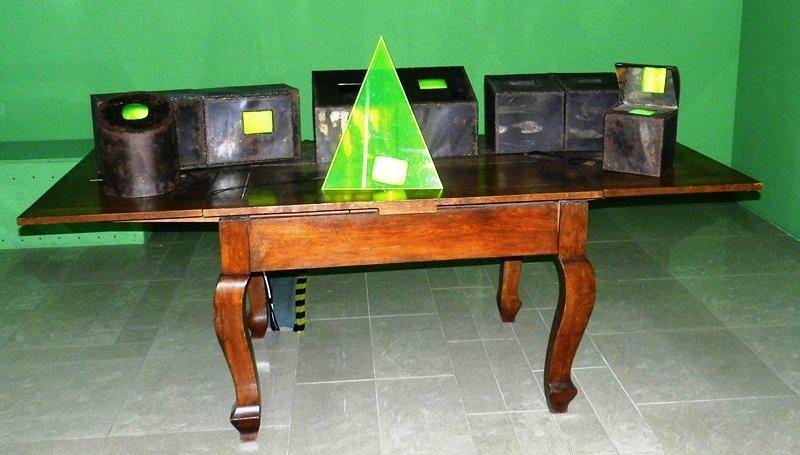 """Kategoria wzrok: Izabella Gustowska instalacja multimedialna """"Odbicia"""" 1994 Instalacja złożona z pięciu stalowych skrzynek oraz stożka z pleksiglasu umieszczonych na prostokątnym, ciemnym stole z drewna. Wewnątrz stożka i na skrzynkach ekrany. Dominuje jaskrawozielona barwa filmowych obrazów emitowanych równocześnie."""