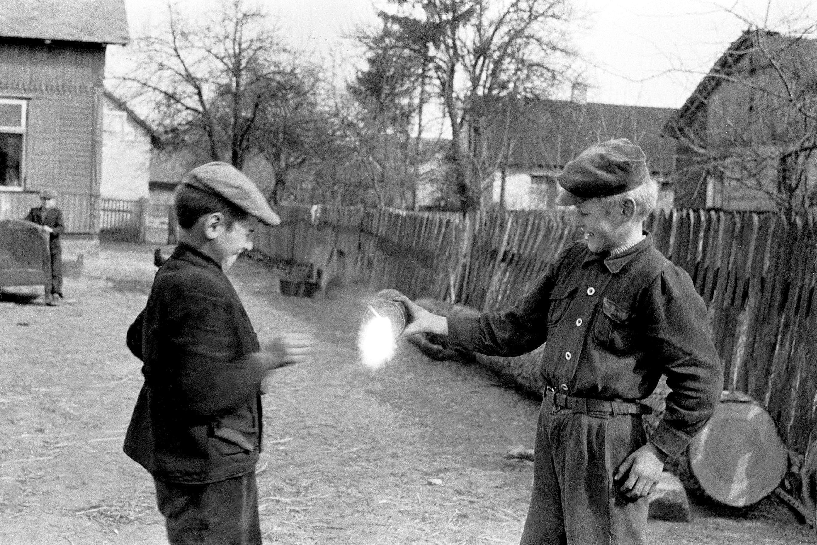 Gocław, powiat Garwolin, 25.03.1959. Zabawy wiejskich dzieci, które rozkręcają pociski armatnie, by wydobyć proch, który pali się w ich rękach pięknym płomieniem. Fot. Aleksander Jałosiński / FORUM