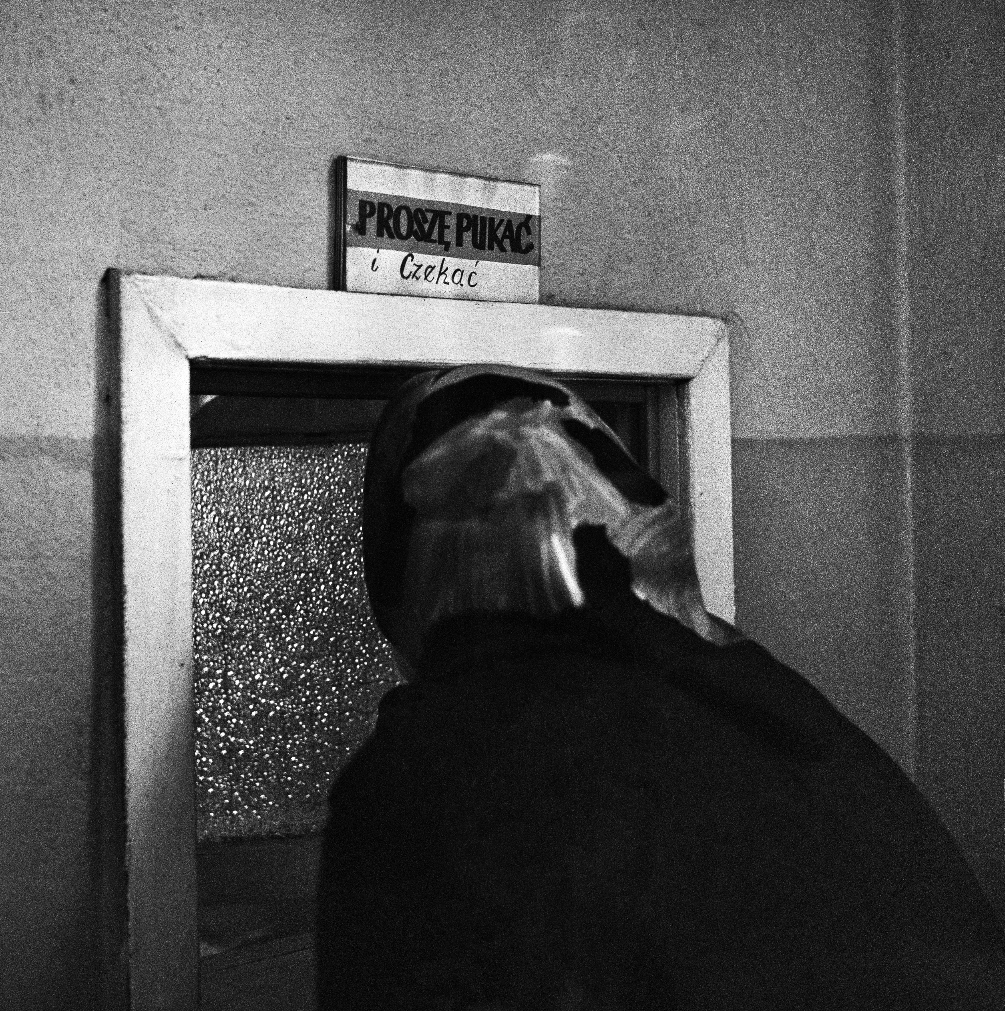 Wrocław, 10.1972. Urząd Miejski, interesantka przed okienkiem z napisem: Proszę pukać i czekać. Fot. Aleksander Jałosiński/FORUM