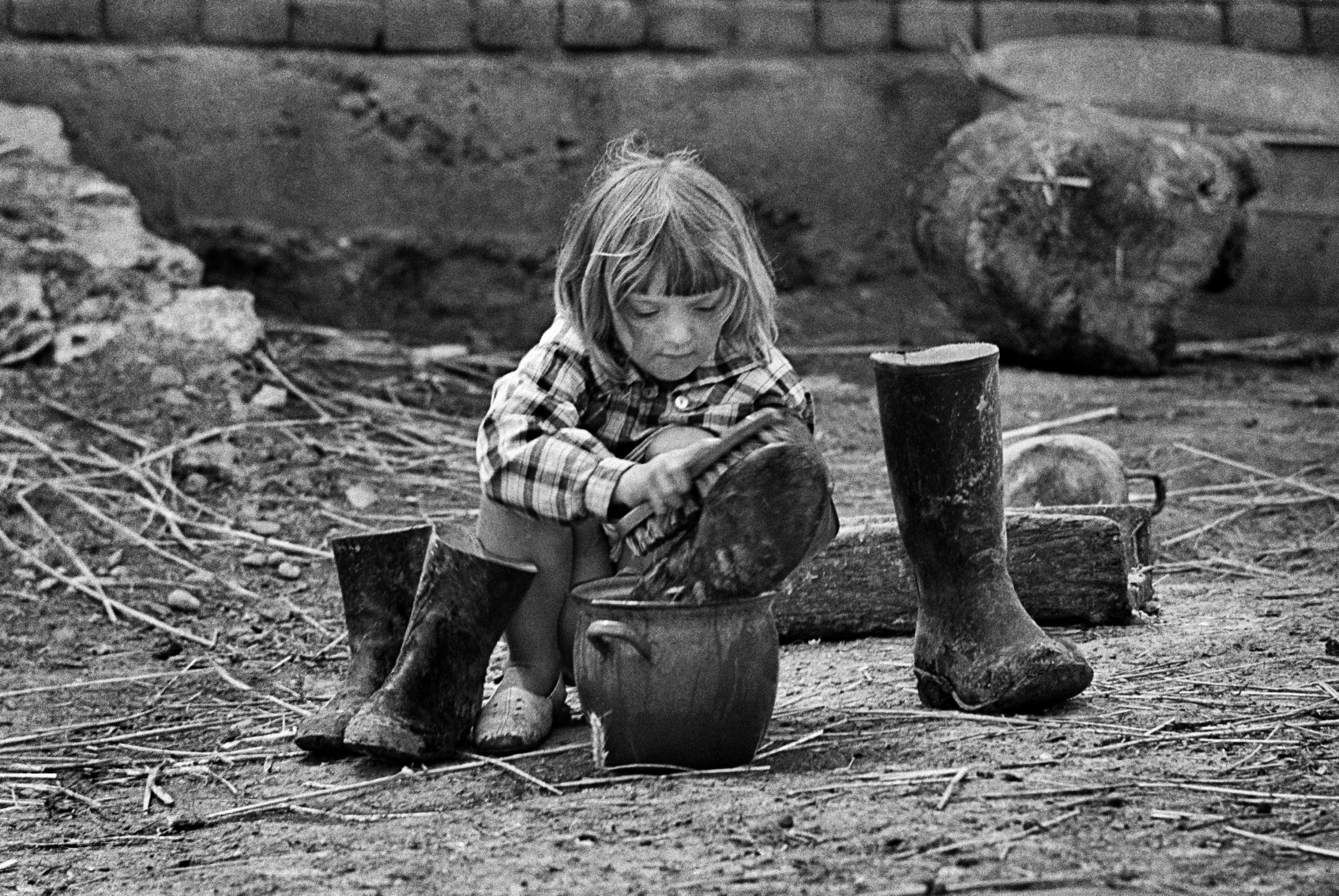 Piekary, Małopolska, 05.1968. Ludzie na wsi, dziewczynka czyści kalosze. Fot. Aleksander Jałosiński/FORUM