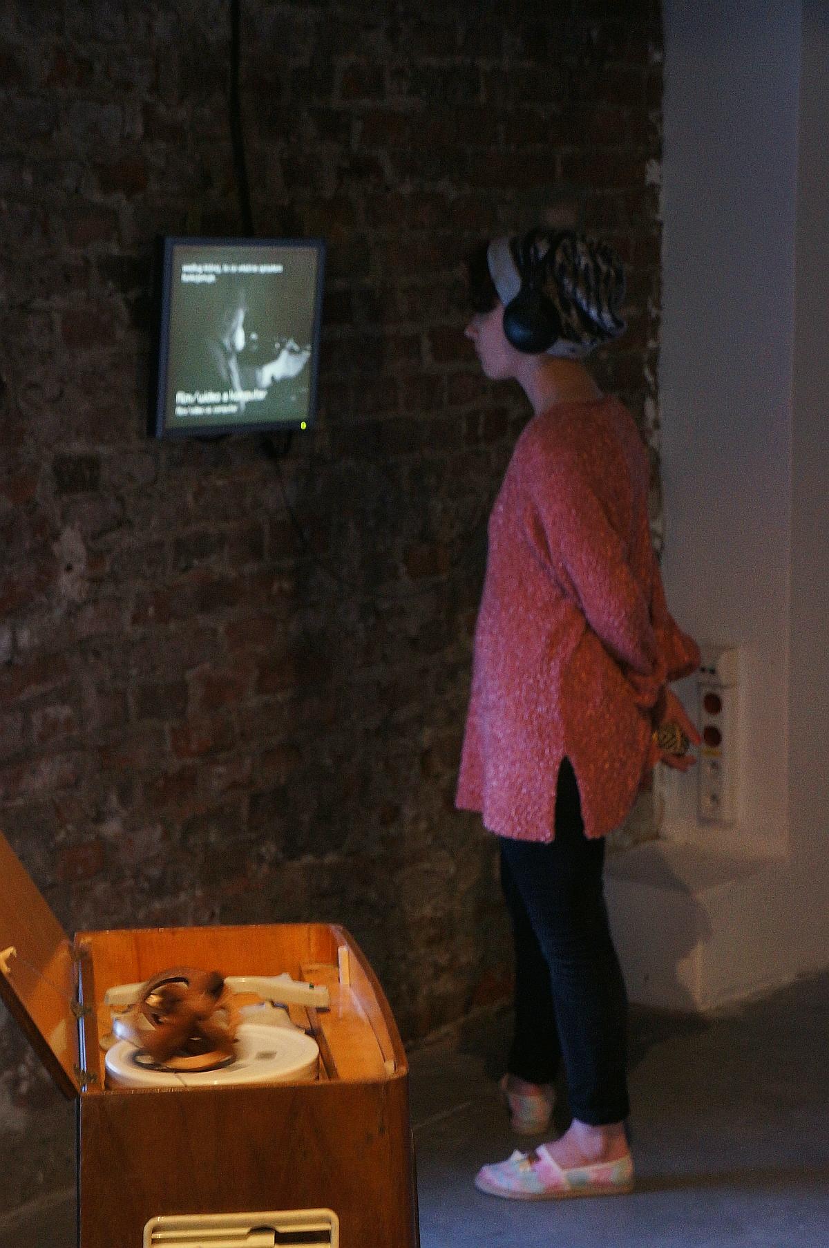 Janine Halka ogląda wywiad z Woodym Vasulką z 1995 r., z Kolekcji WRO Zmienne-Stałe-Błądzące. AC/DC/IT, wystawa WRO Art Center, fot. WRO