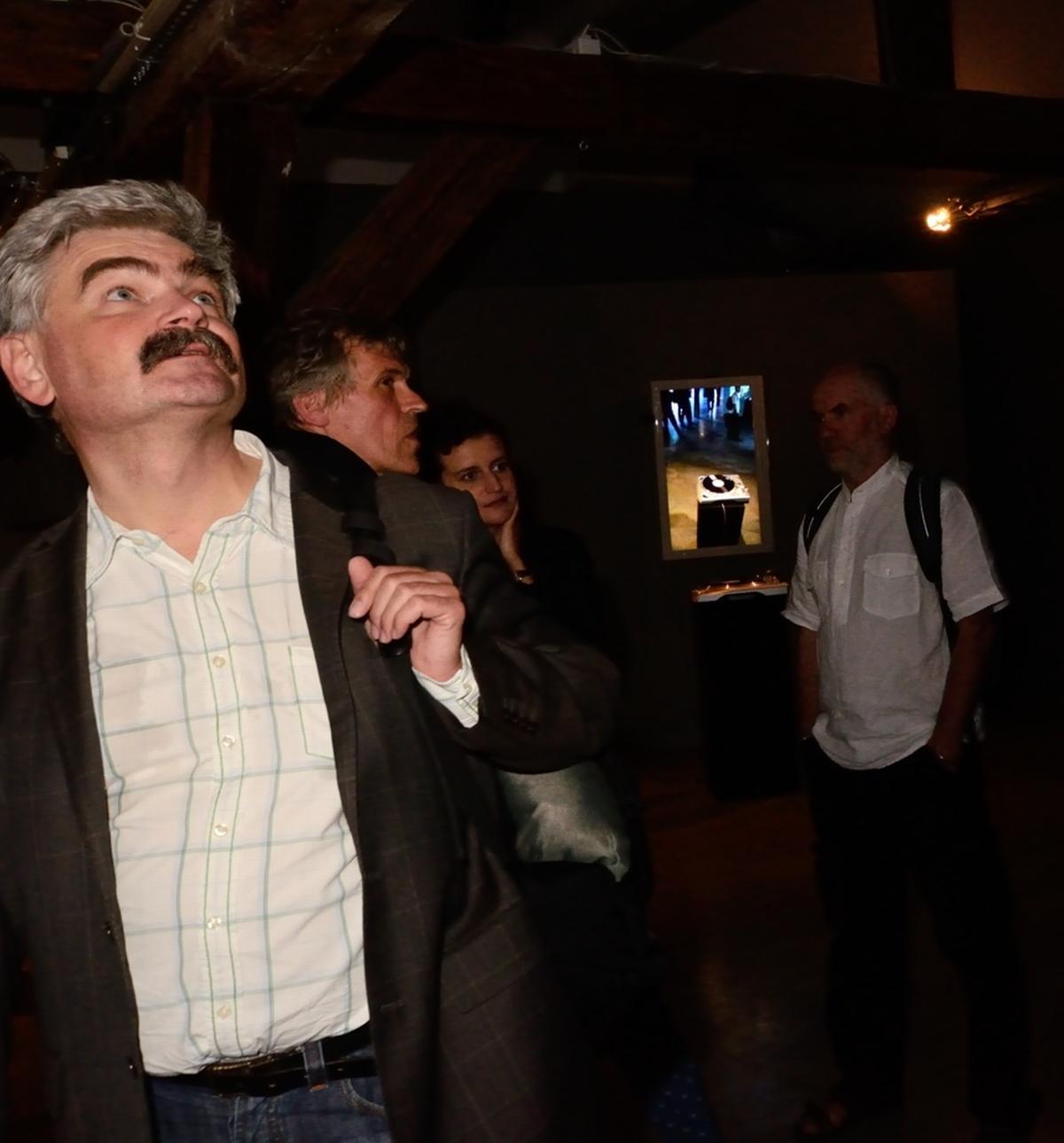 Edwin Bendyk, za nim Piotr Krajewski i Ola Wasilkowska podczas oprowadzanie po wystawie, w głęgi instalacja Pawła Janickiego Vinyl Video Delay. Zmienne-Stałe-Błądzące. AC/DC/IT, wystawa WRO Art Center, fot. WRO