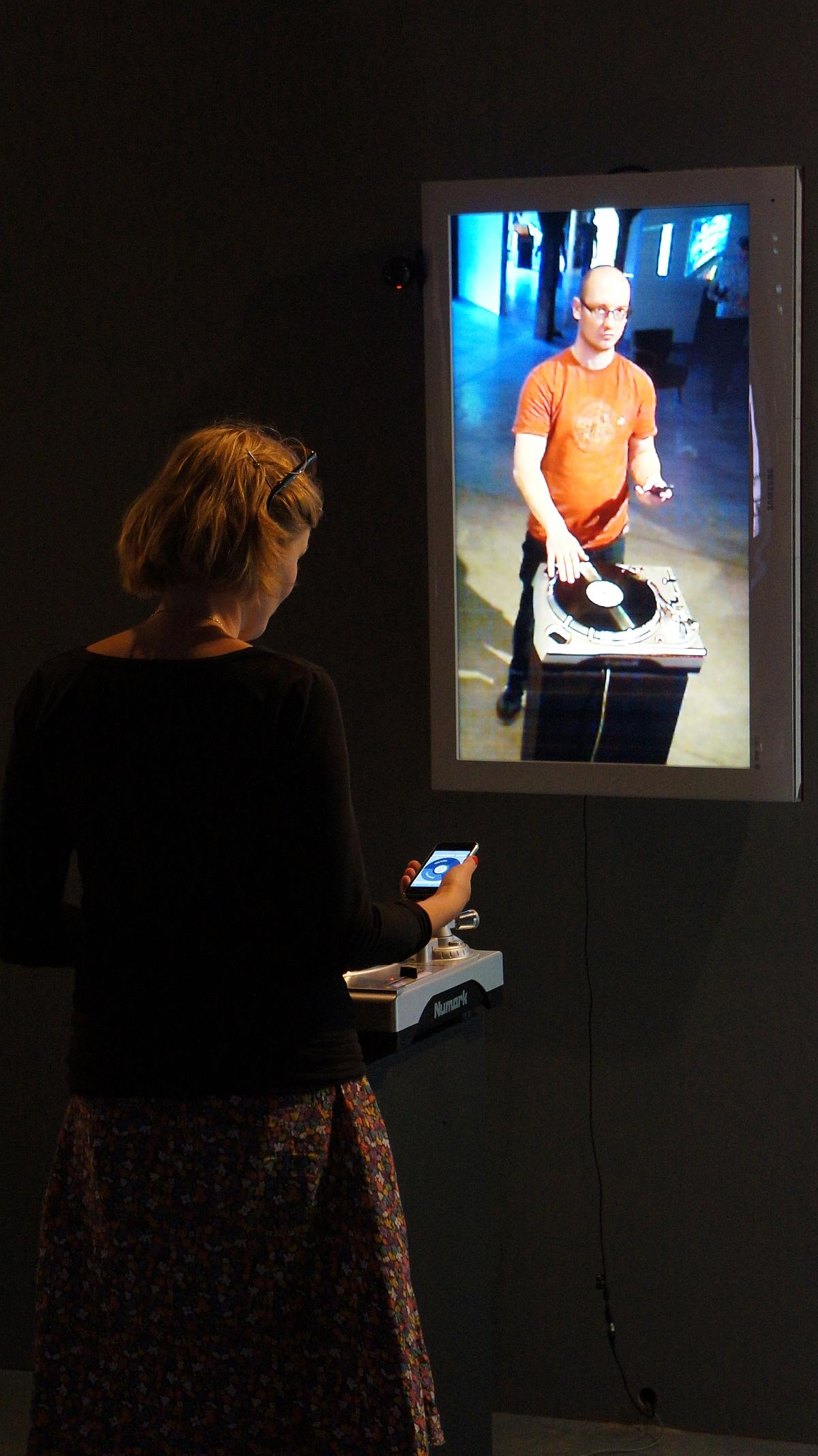 Gosia Gawlik steruje instalacją Pawła Janickiego Vinyl Video Delay, miksując zarejestrowaną wcześniej sylwetkę Bartosza Koniecznego. Zmienne-Stałe-Błądzące. AC/DC/IT, wystawa WRO Art Center, fot. WRO