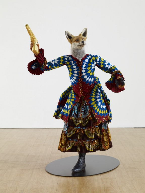 "Yinka Shonibare ""Revolution Kid (fox girl)"", 2012. Mannequin, Dutch wax printed cotton, fibreglass, leather, taxidermy fox head, steel base plate, BlackBerry and 24 carat gold gilded gun 44 x 36 x 30 inches (źródło: materiały prasowe organizatora)"