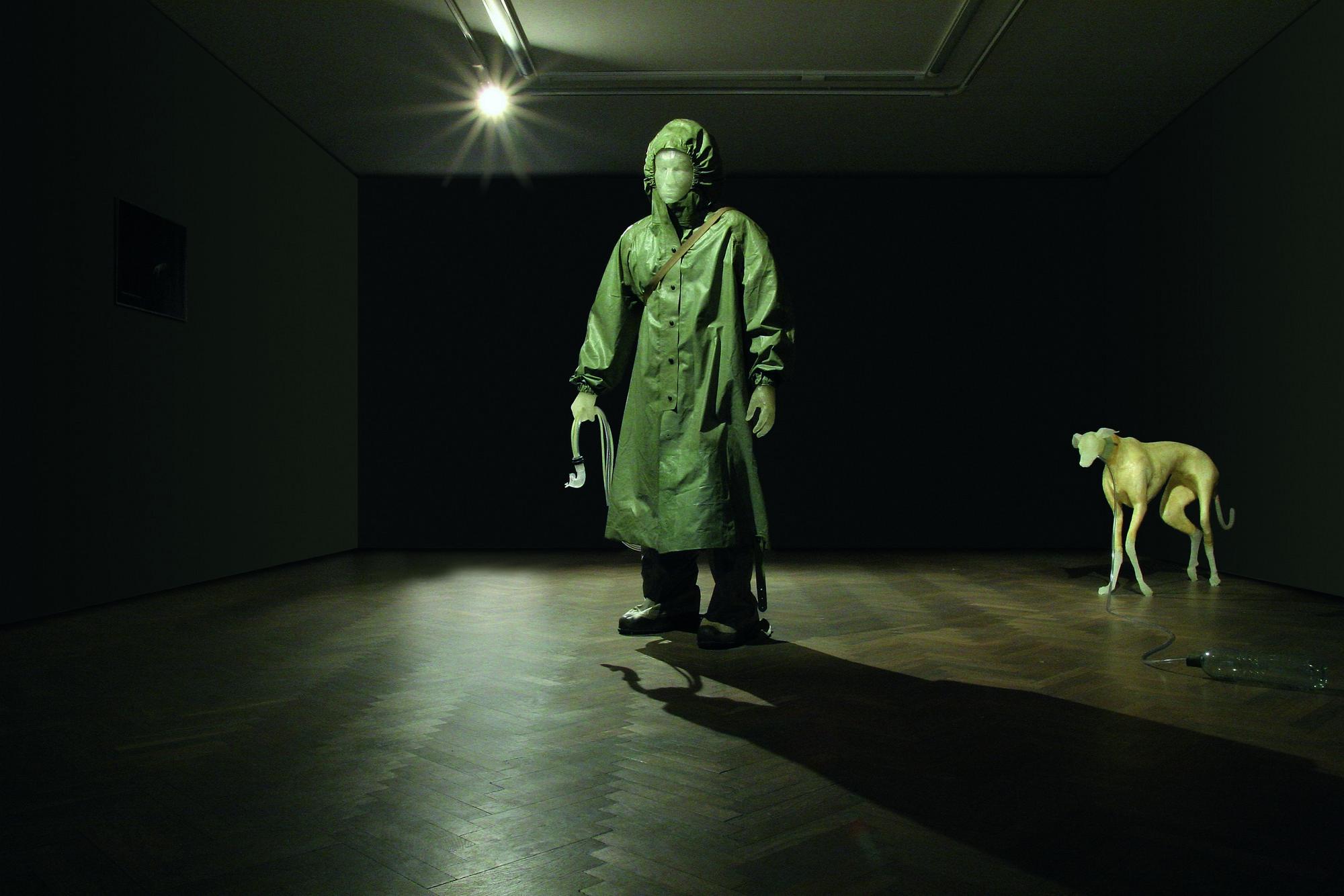 """Kuba Bąkowski, """"Chłopiec i jego pies"""", 2006, rzeźba, żywica epoksydowa, styropian, wojskowe ubranie ochronne, butelka PET, rurki plastikowe (źródło: materiały prasowe organizatora wystawy)"""