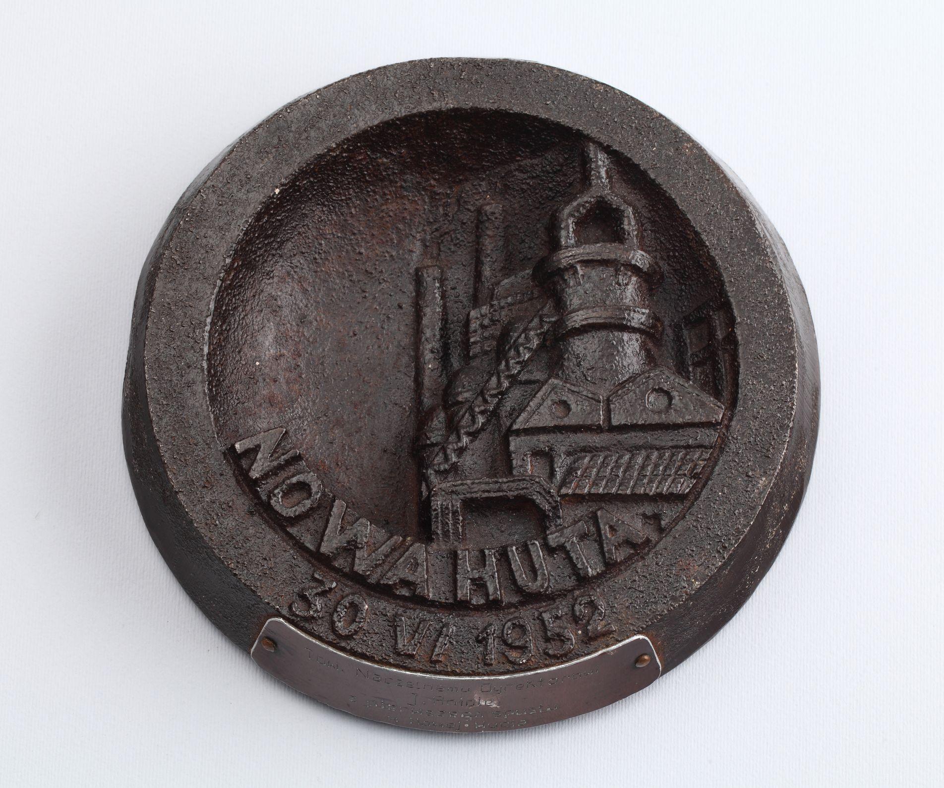 Popielniczka z pierwszego spustu surówki, z metalu w kolorze czarnym. Wewnątrz czaszy napis NOWA HUTA i widok Wielkiego Pieca (od lewej: dwa kominy, taśmociąg, dachy budynków, a nad nimi walec zwieńczony dwoma kominami). Na obrzeżu napis: 30 VI 1952. Na brzegu popielniczki plakietka z jasnego, galwanizowanego na ciemno metalu z wytłoczonym napisem: Tow. Naczelnemu Dyrektorowi / J. Aniole / z pierwszego spustu / w Nowej Hucie, 30 VI 1952, dar Stowarzyszenia na Rzecz Rozwoju Nowej Huty dla Muzeum, wł. MHK (źródło: materiały prasowe organizatora)