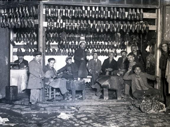 """Zakład szewski. Część butów posiada przydeptane pięty, co do dziś jest tradycyjnym sposobem """"modyfikowania"""" obuwia przez właścicieli, którzy muszą je często ściągać. Fotografia, lata 30. XX w., autor nieznany, Kolekcja fotografii Suna ve İnan Kıraç Vakfı (źródło: materiały prasowe organizatora)"""